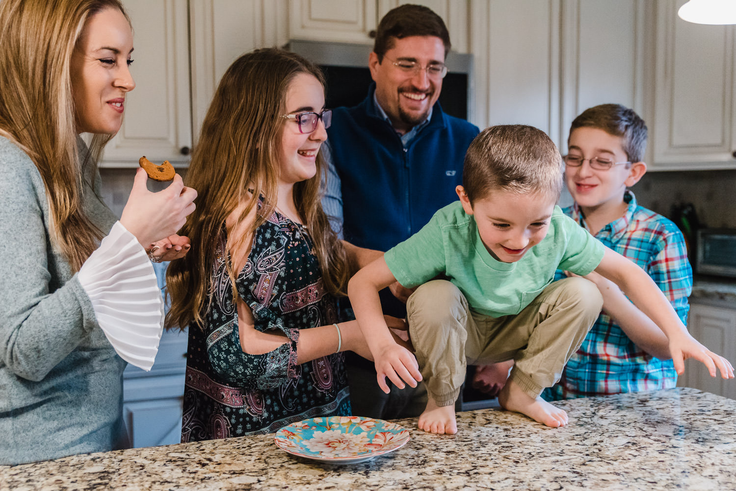 A family laughs together in the kitchen.