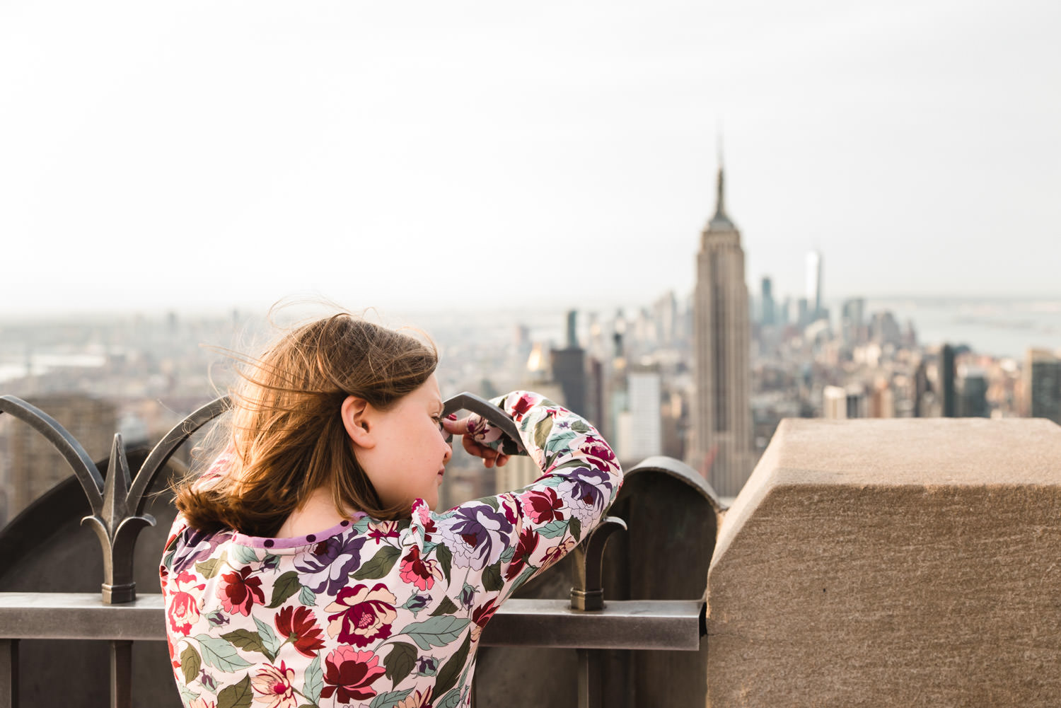 A girl looks at the view of the Empire State Building at Top of the Rock.