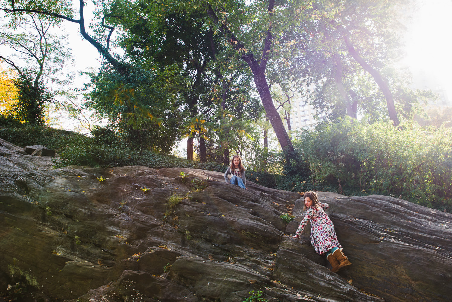 Two girls climb the rocks in Central Park.