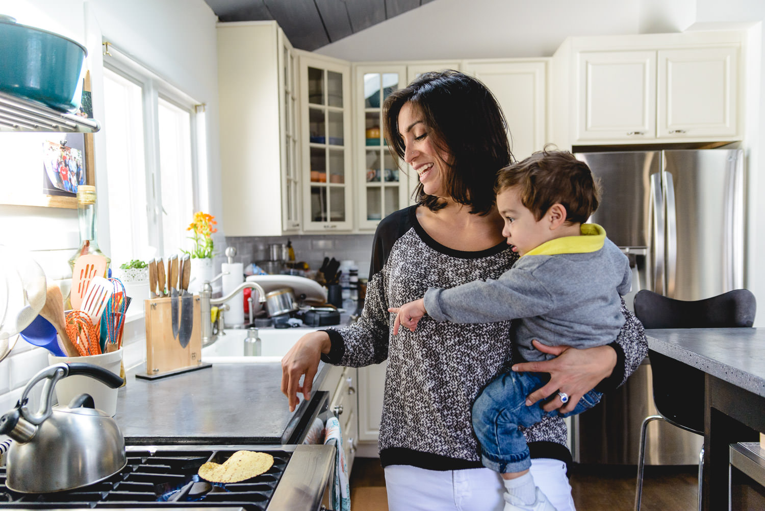 A mother cooks a tortilla while holding her young son.