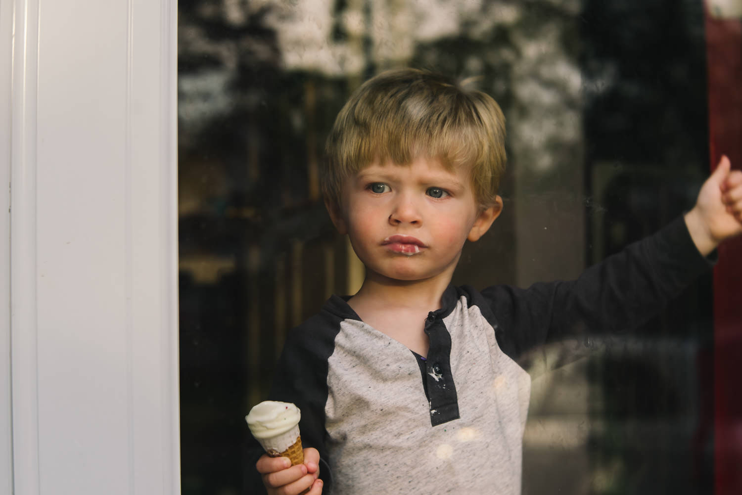 A little boy eating an ice cream cone looks out the storm door.