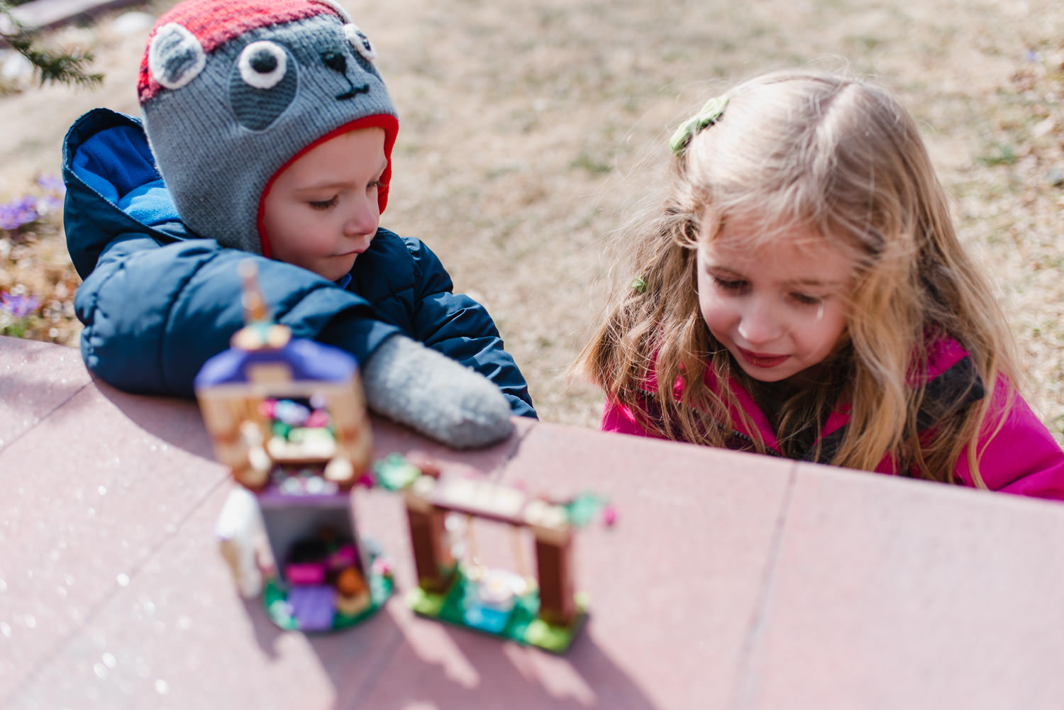Siblings play with legos in their front yard.