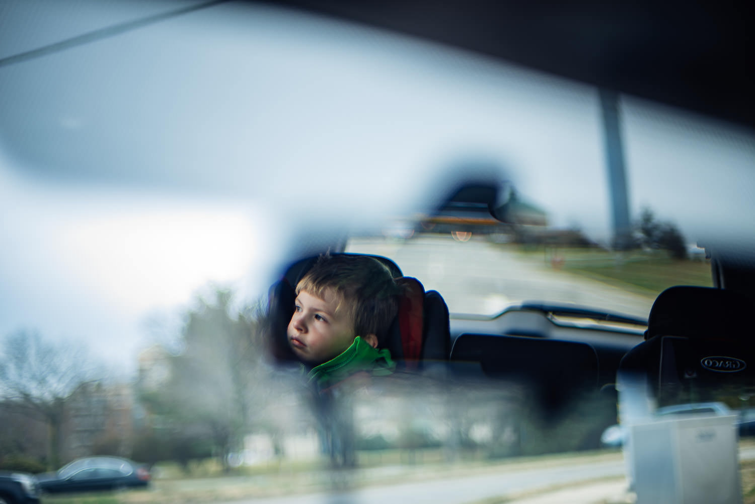 A reflection of a little boy in a rearview mirror.