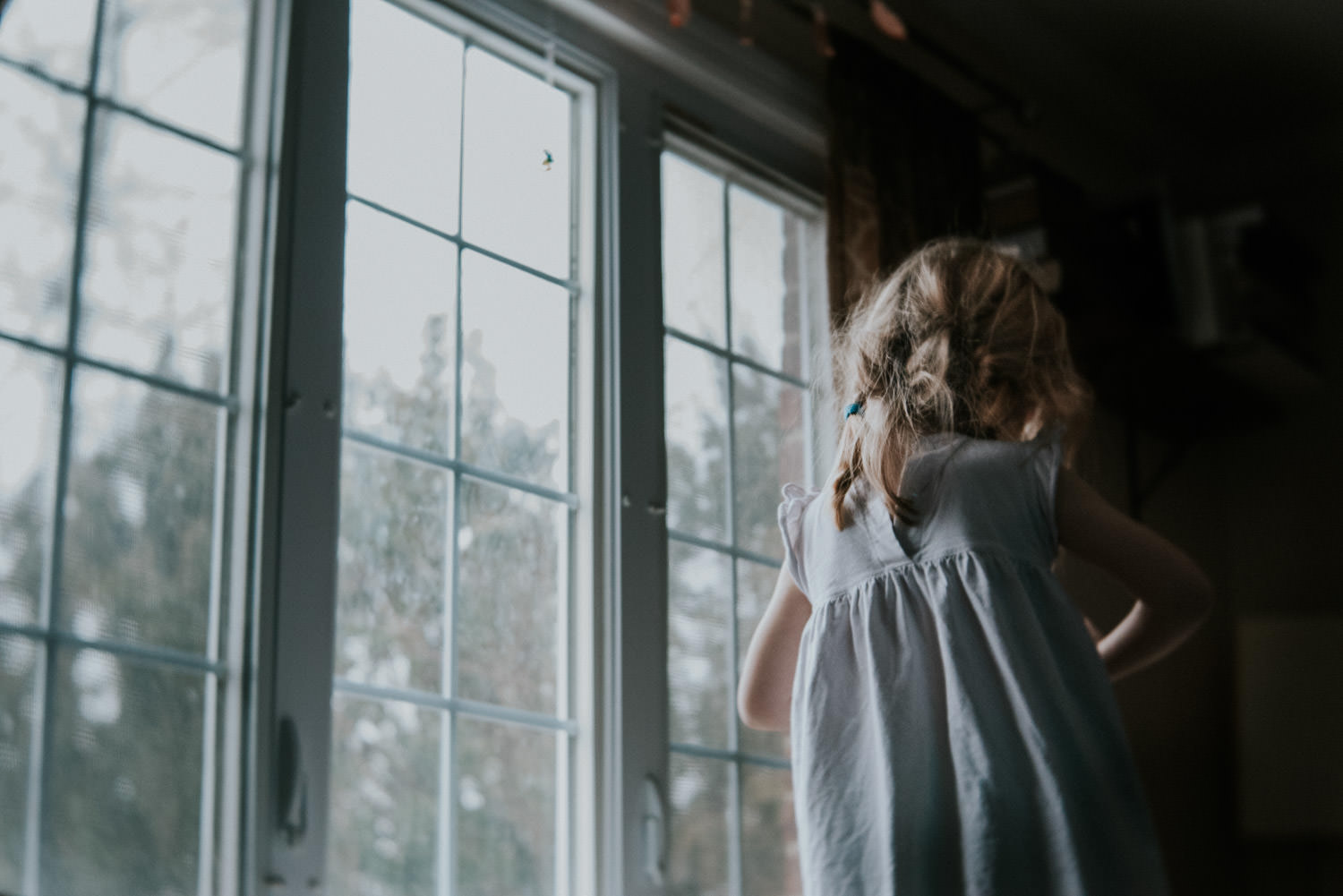 A little girl stands in front of a large window.