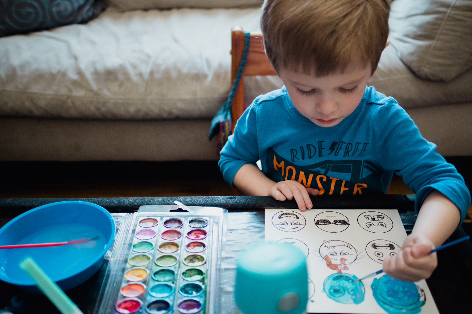 A little boy paints with watercolors.
