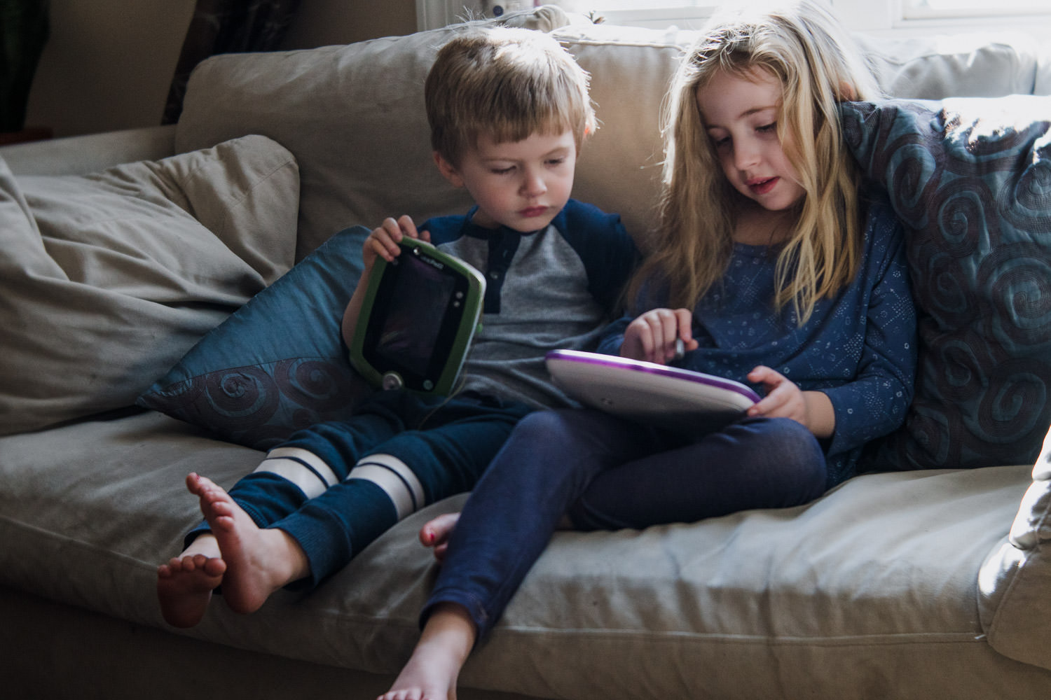 Two children sit on a couch and play with a tablet.