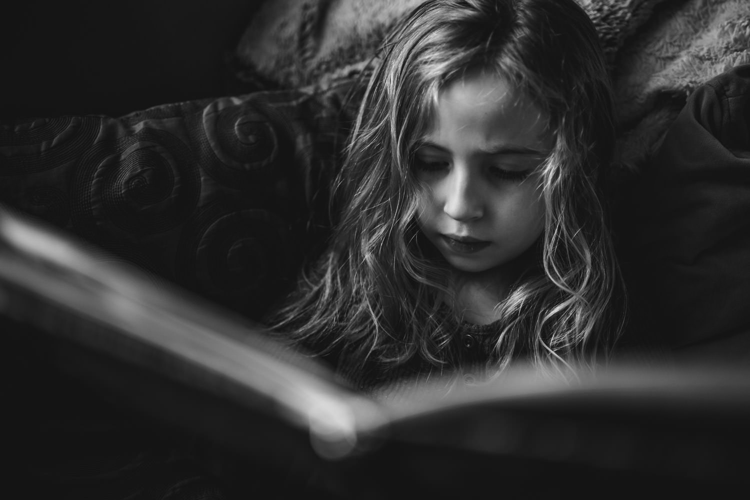 A little girl reads a book.