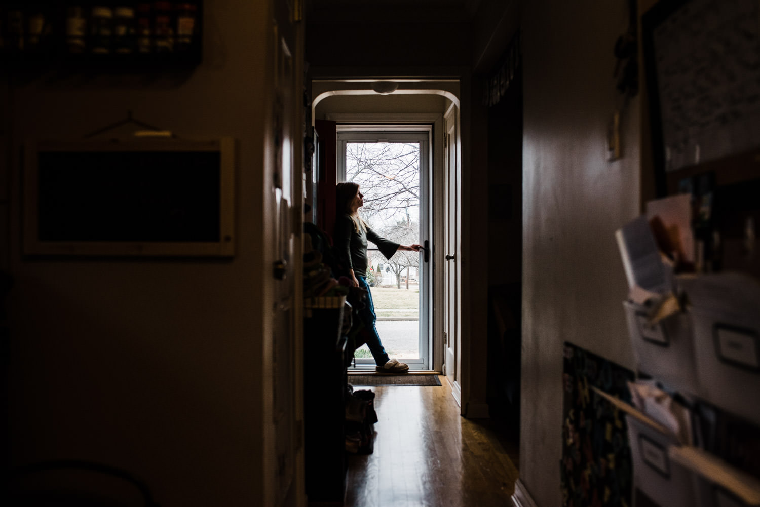 A woman stands in a doorway.