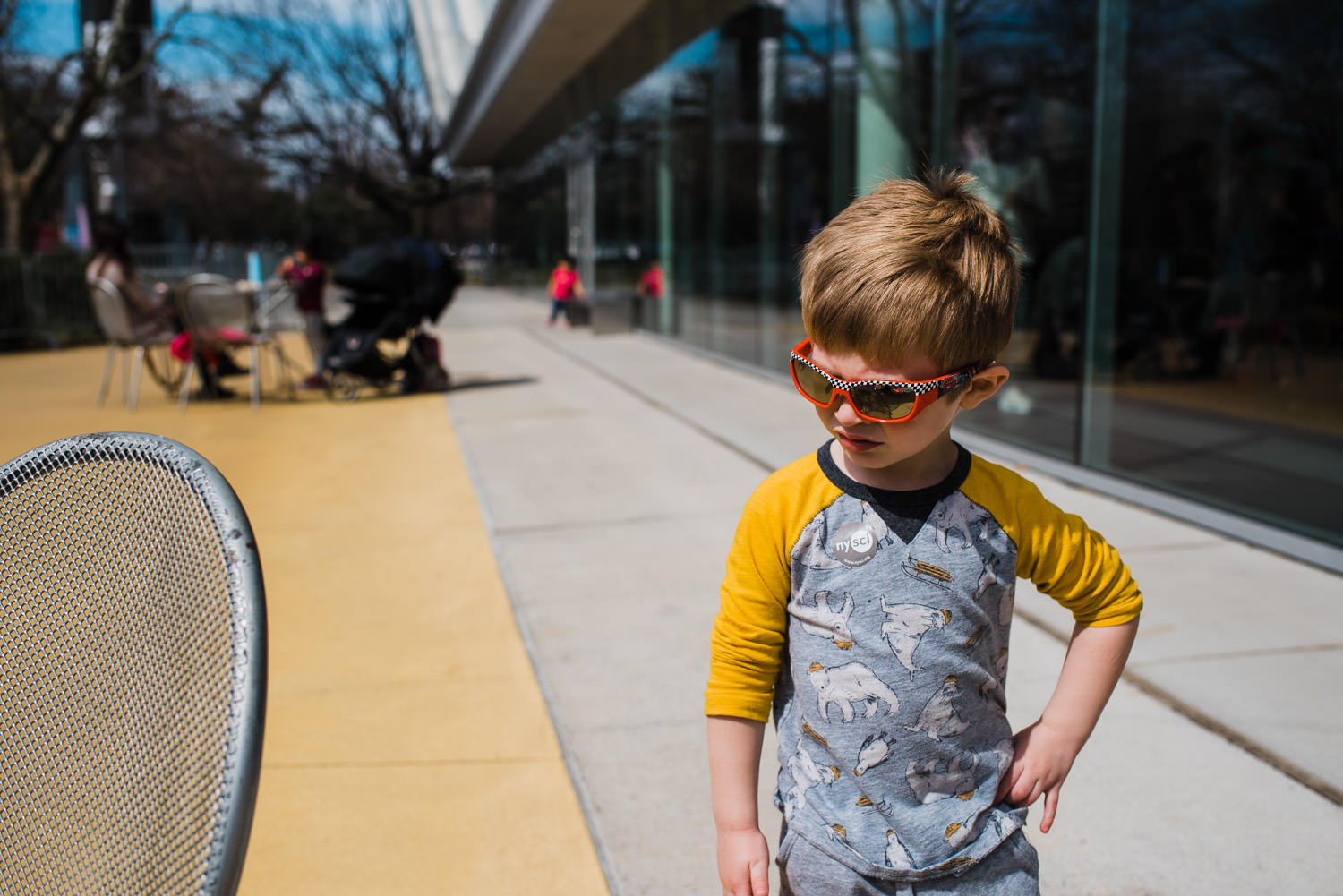 A little boy poses in sunglasses.