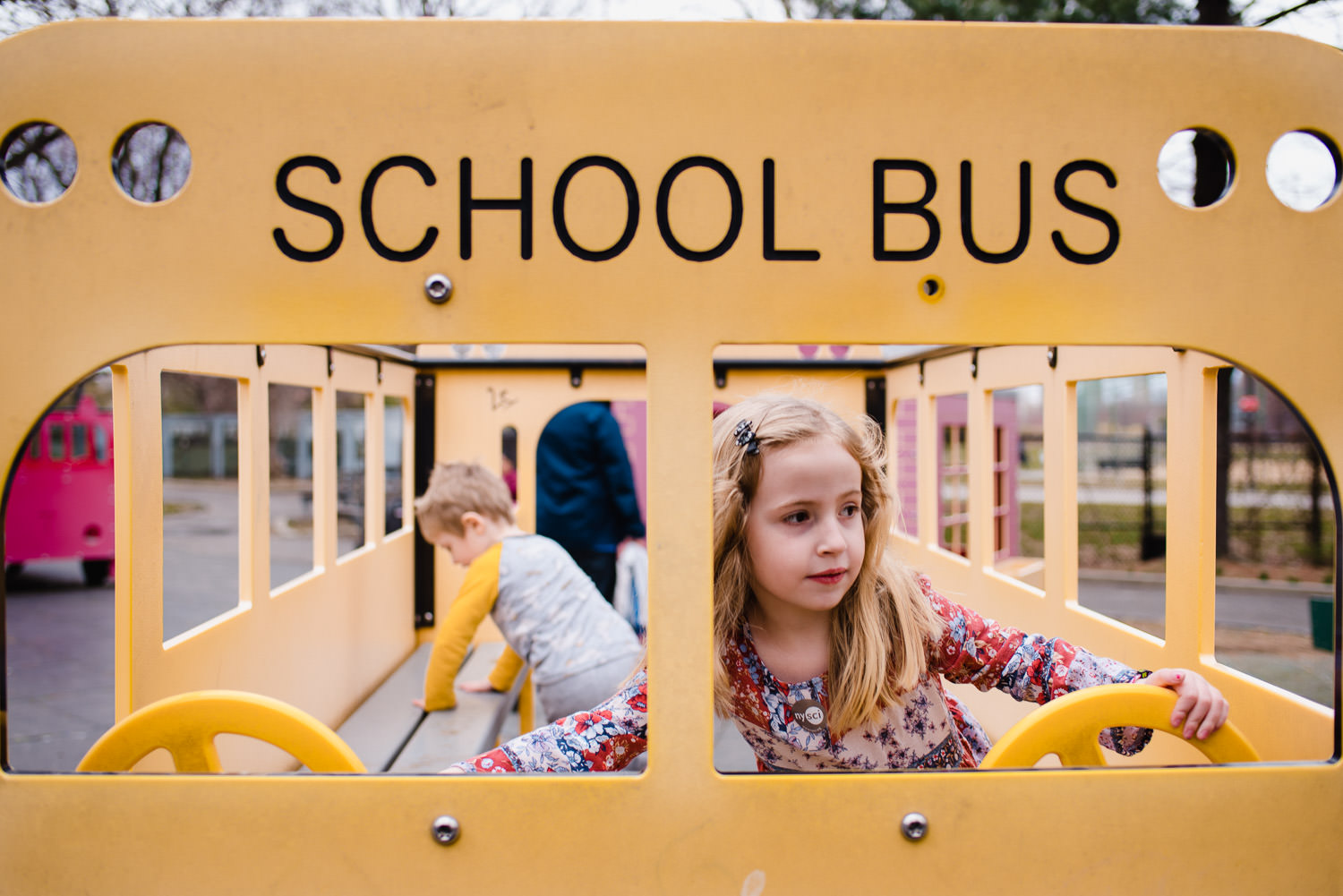 Children play on a school bus structure at a playground.