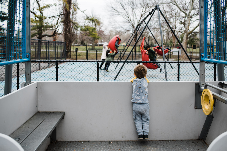 A little boy watches kids on the swings.