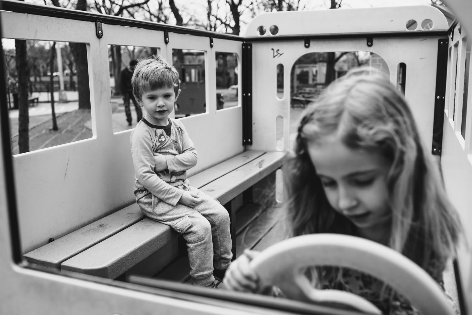 Two children play on a schoolbus structure at a playground.