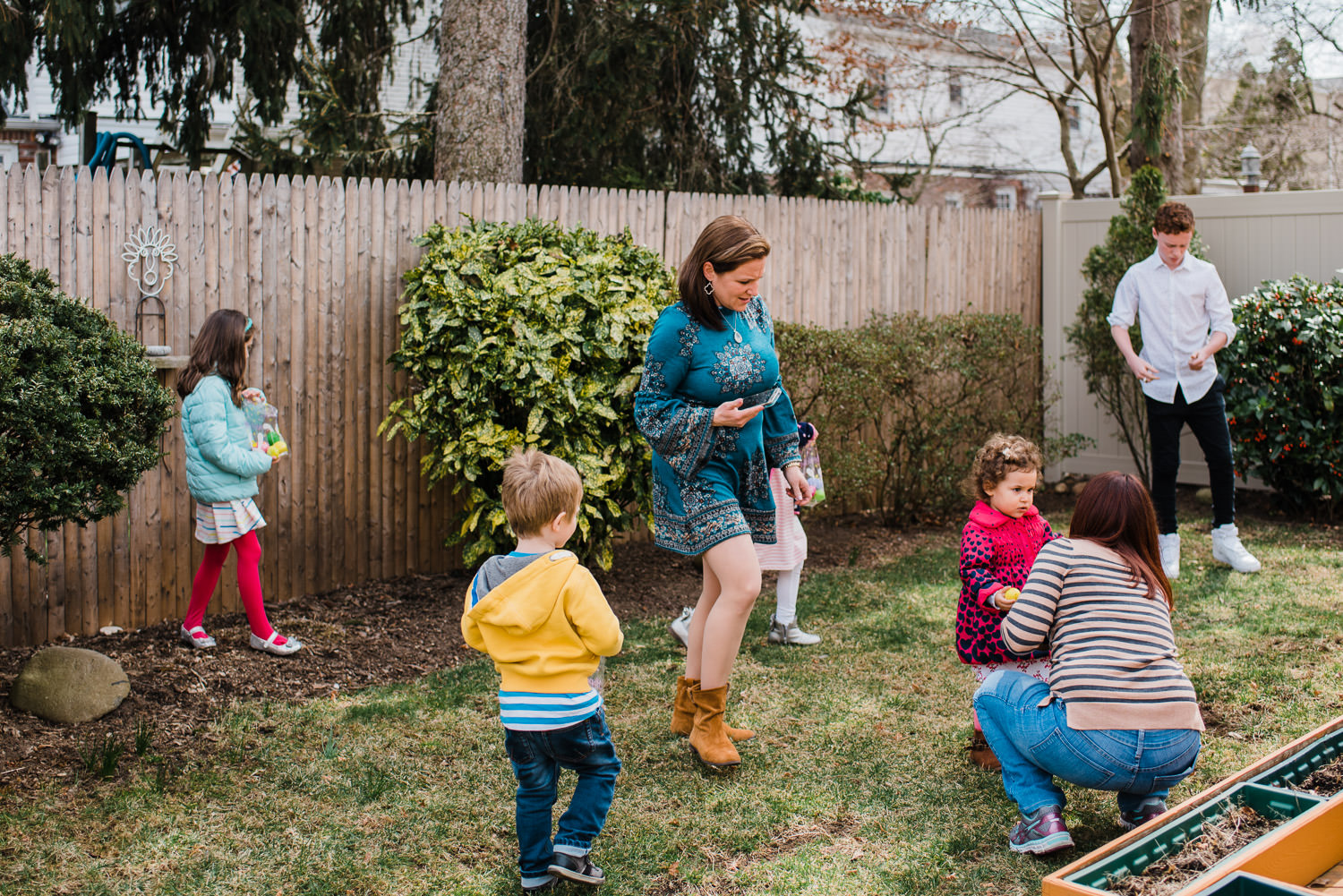 Kids search for Easter eggs in a backyard.