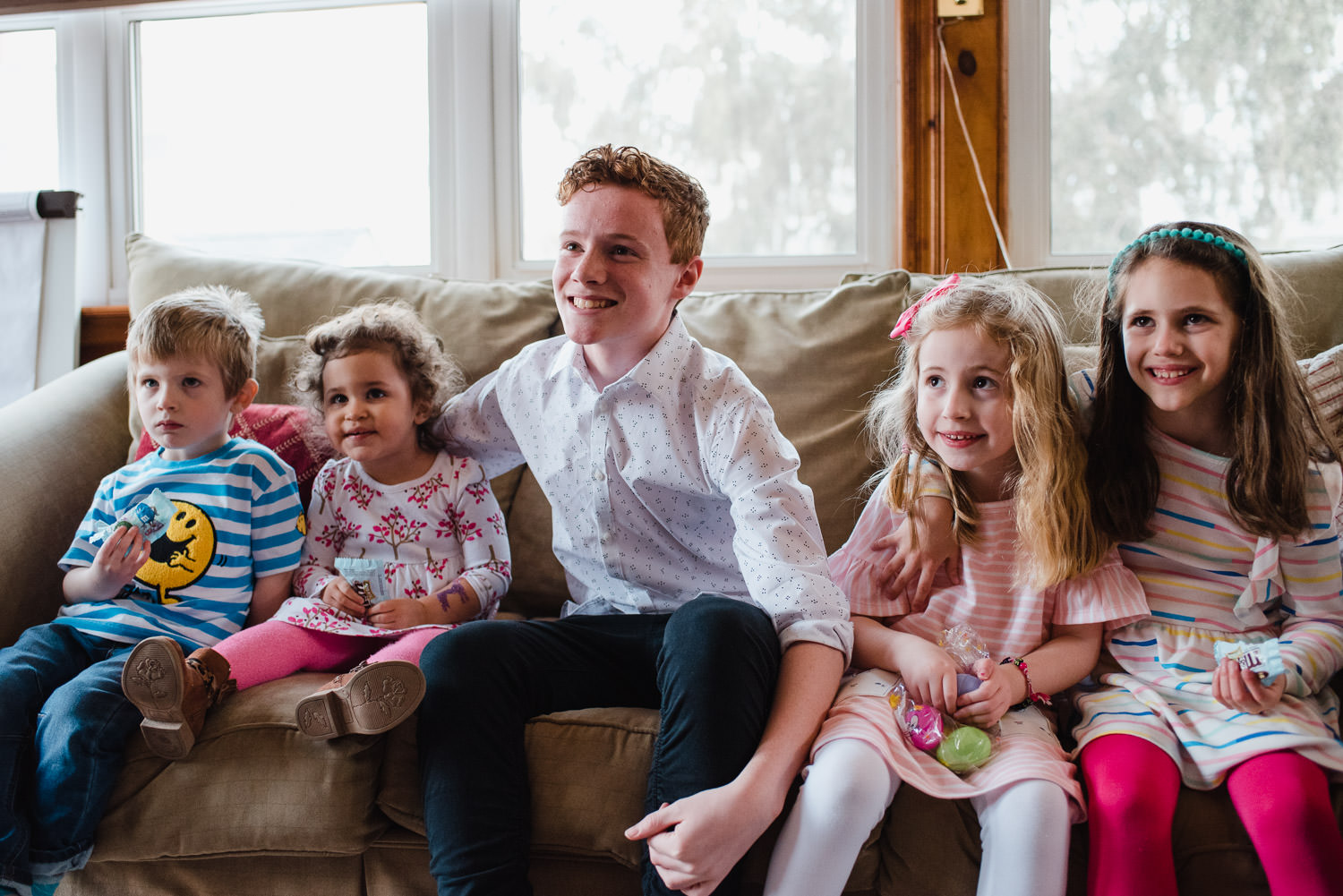 Children pose for a portrait on a couch.