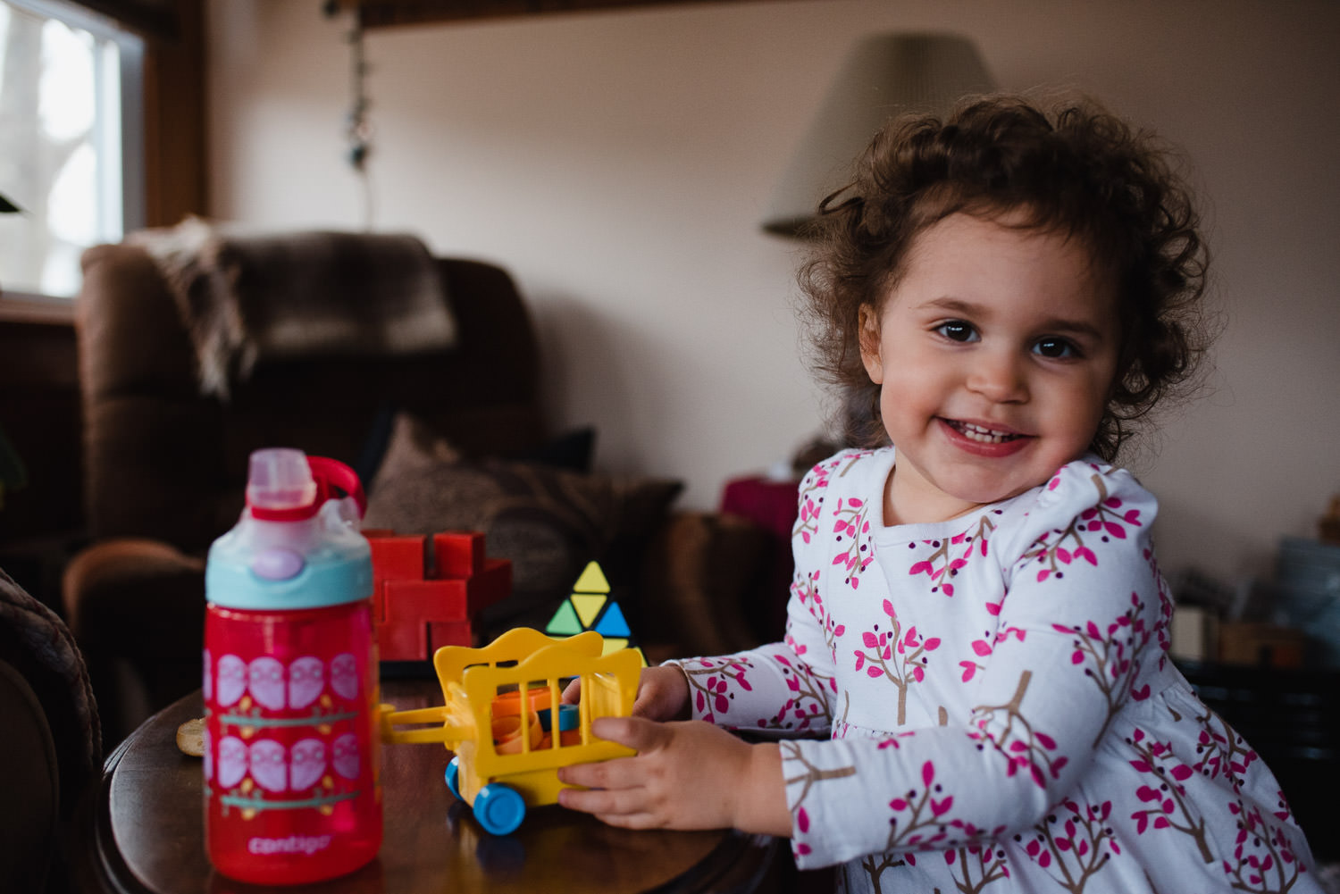 A toddler girl smiles in her living room.