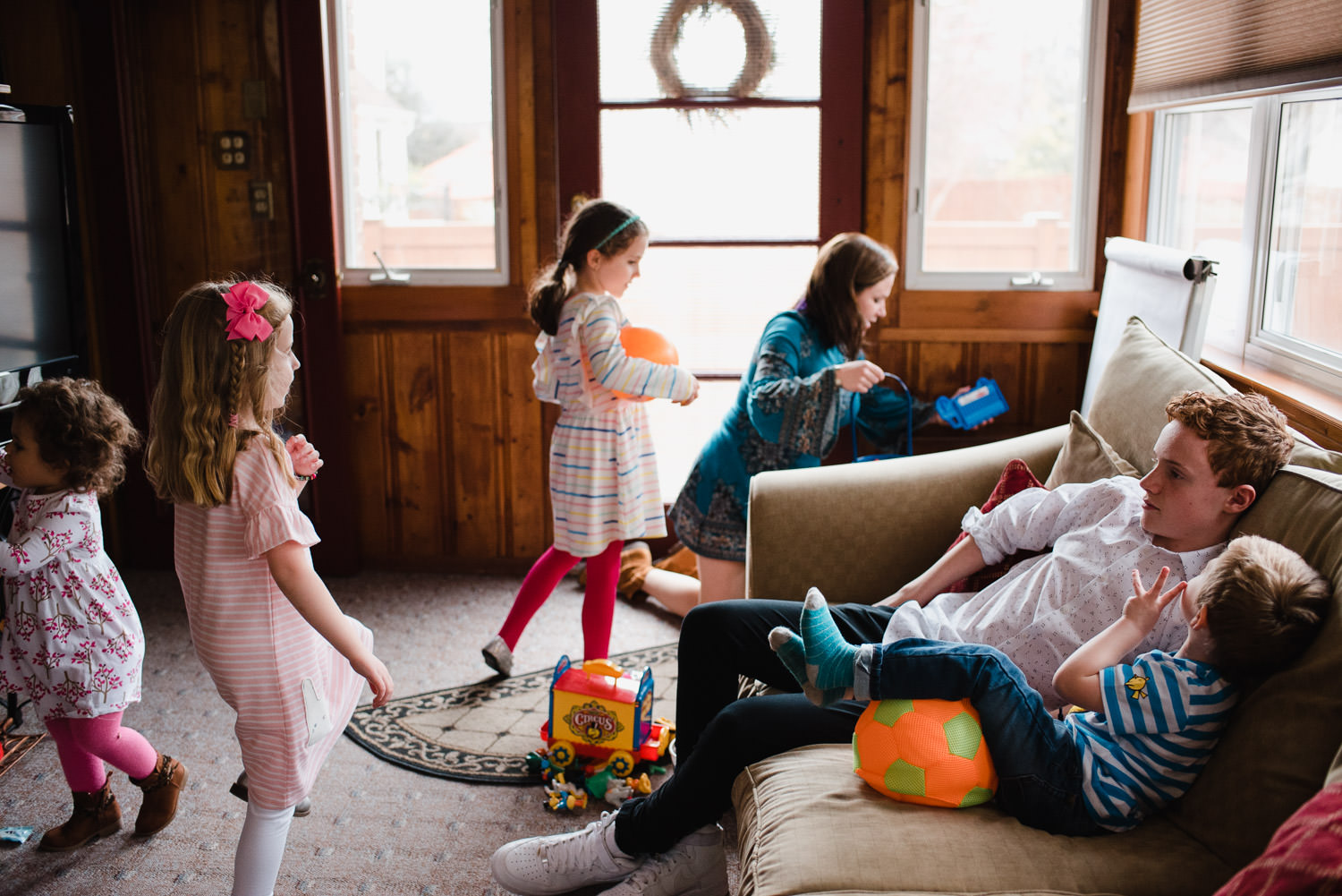 Kids play in the sunroom of a house.