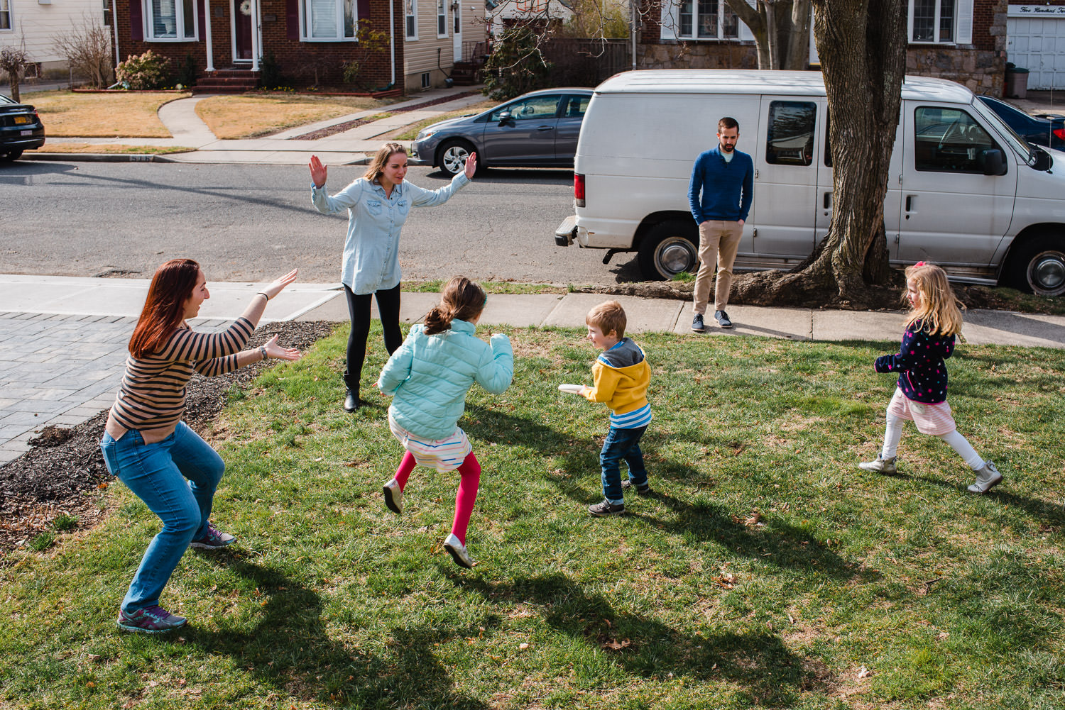 Kids play frisbee in the front yard.
