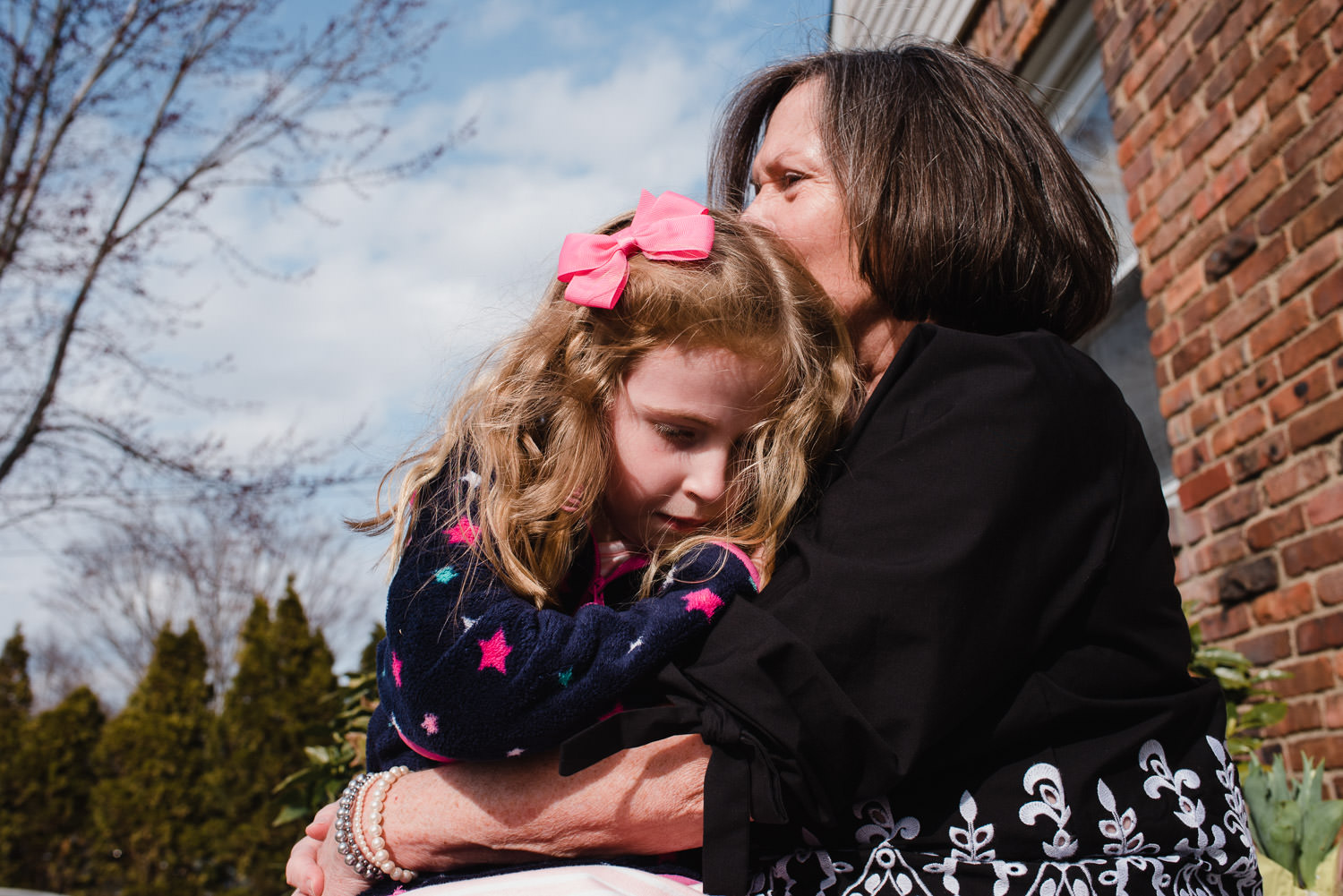 A little girl is embraced by her grandmother.
