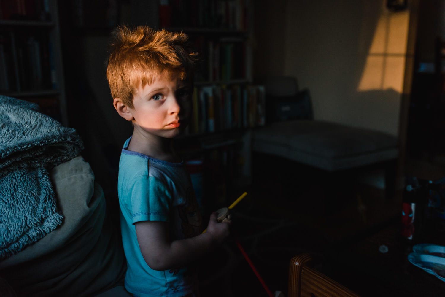 A little boy stands in the living room in a patch of light.