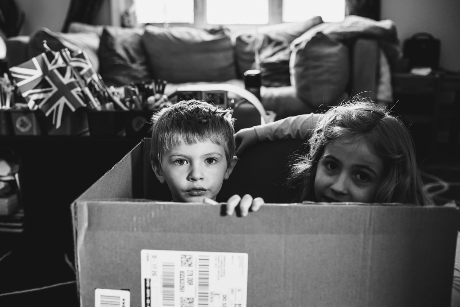 Two children play inside a cardboard box.