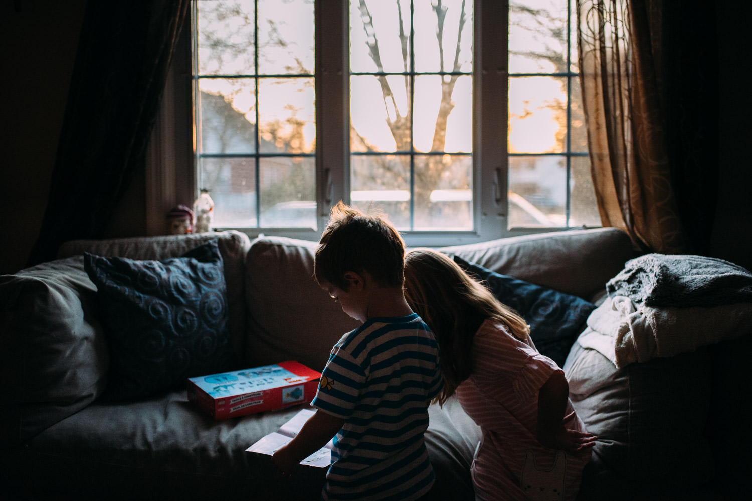 Two kids stand in front of a living room window at sunrise.