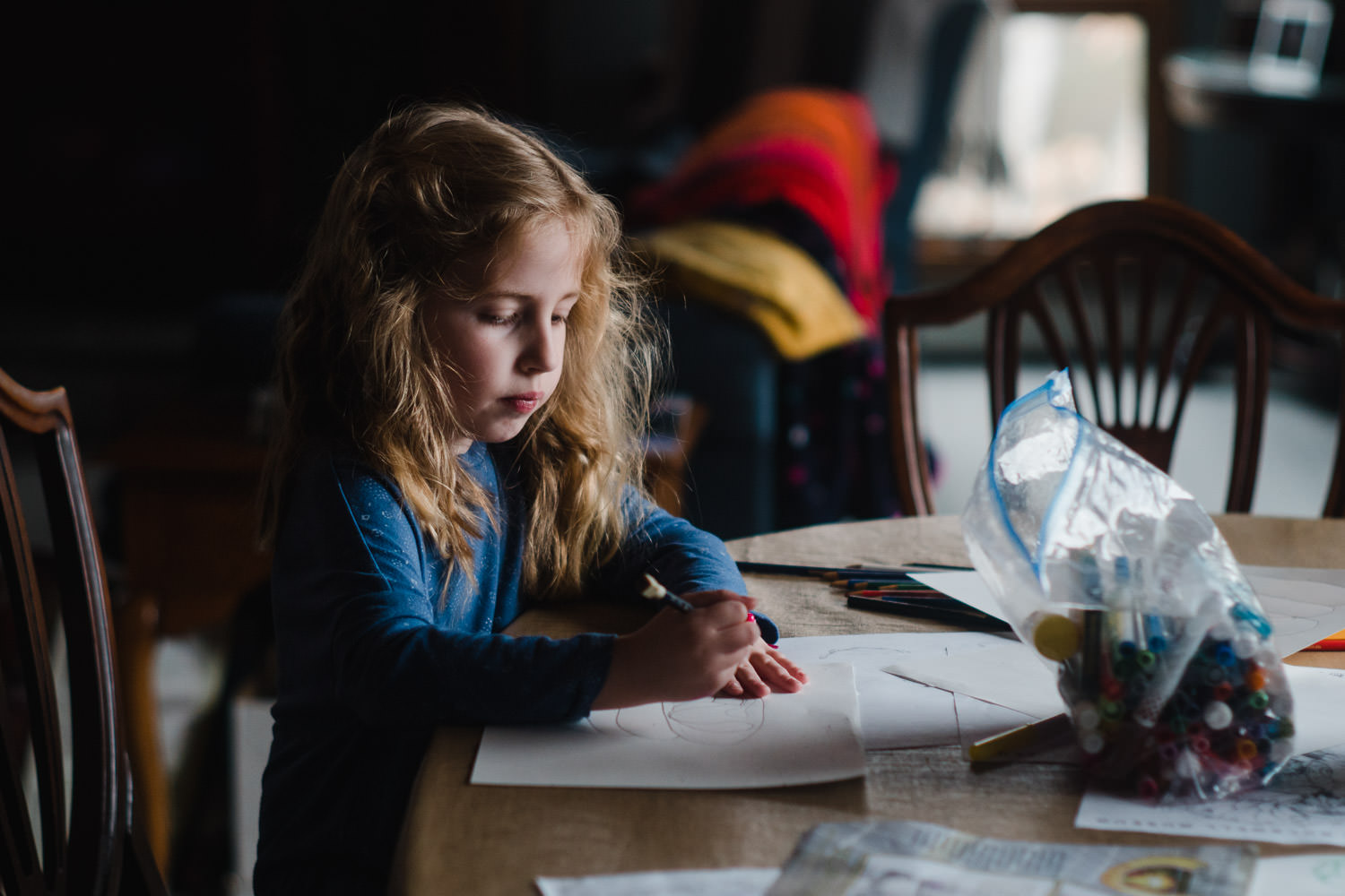 A little girl draws at a table.
