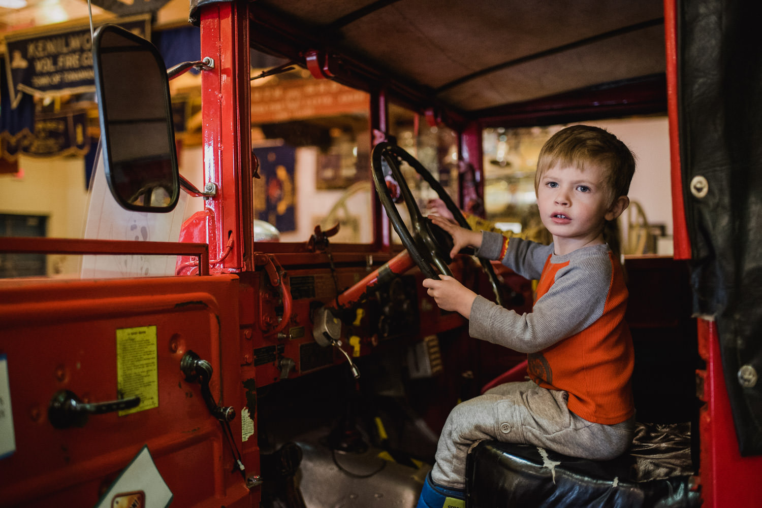 A little boy plays in a fire truck at the fire museum in Hudson, NY.