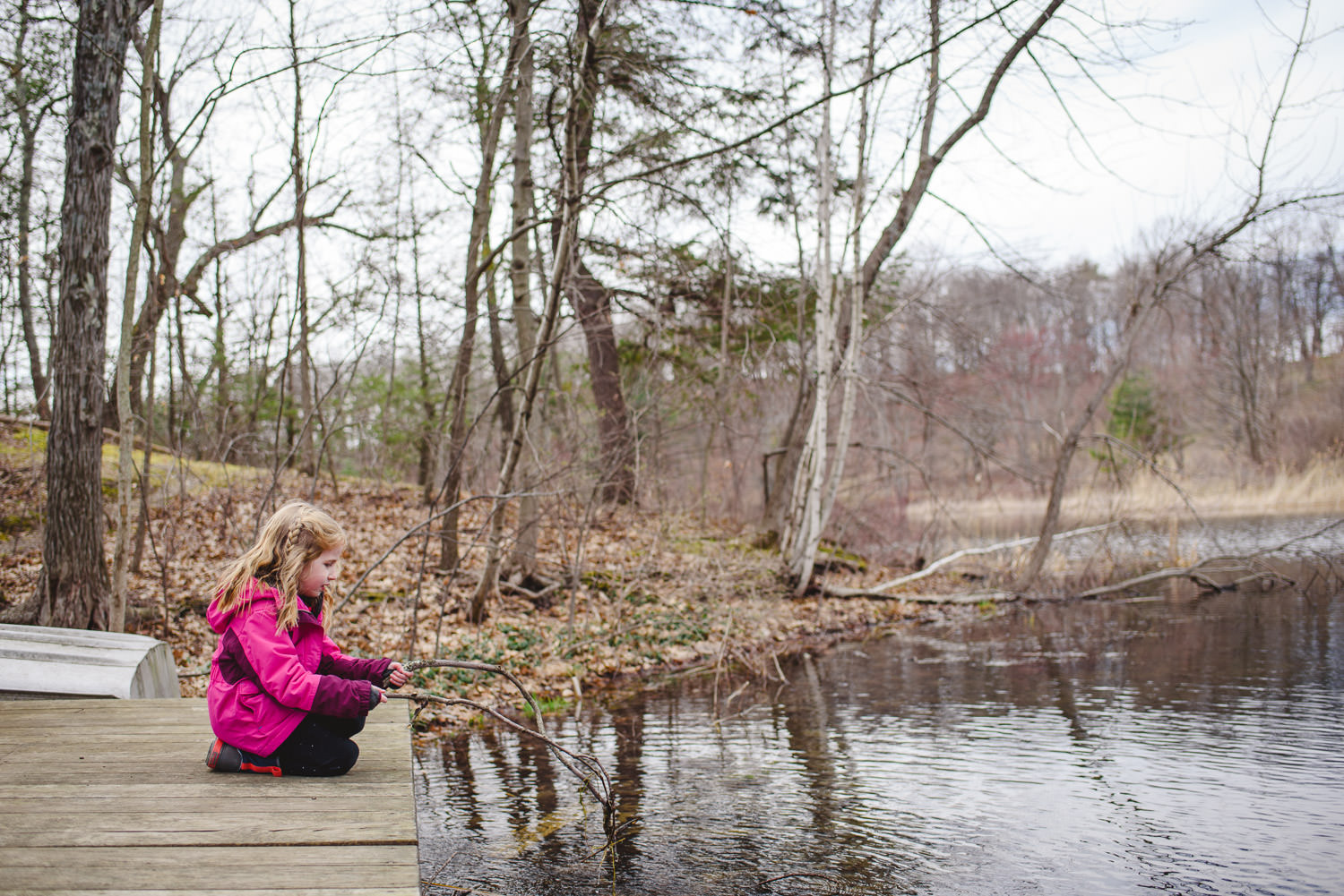 A little girl pretends to fish on a dock.