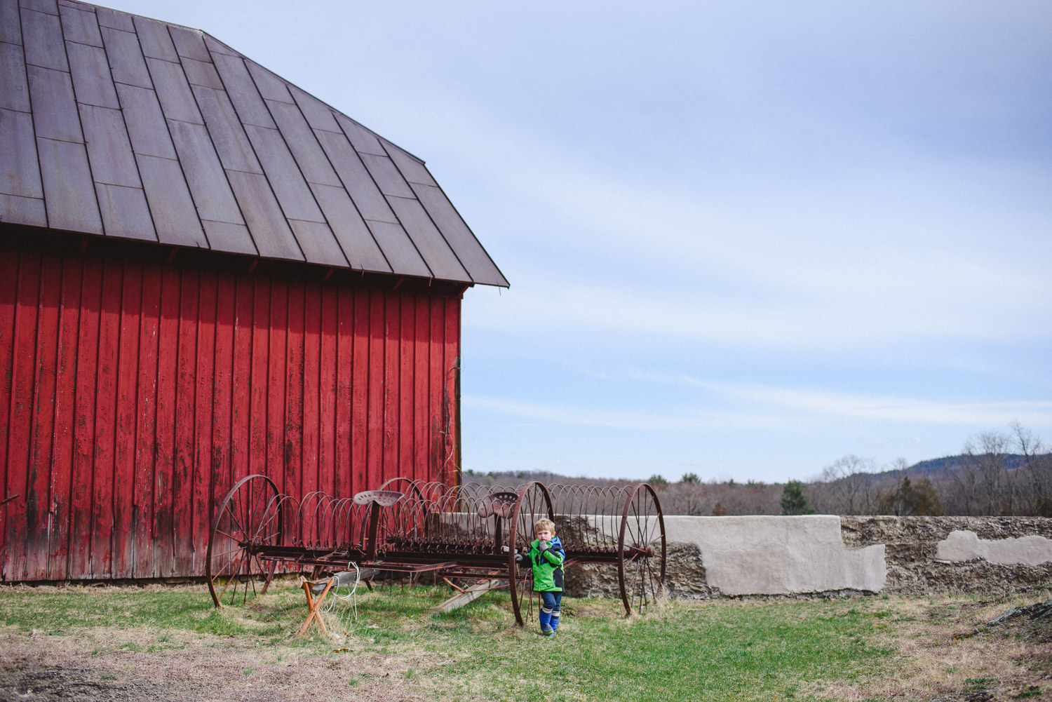 A little boy stands outside a red barn.