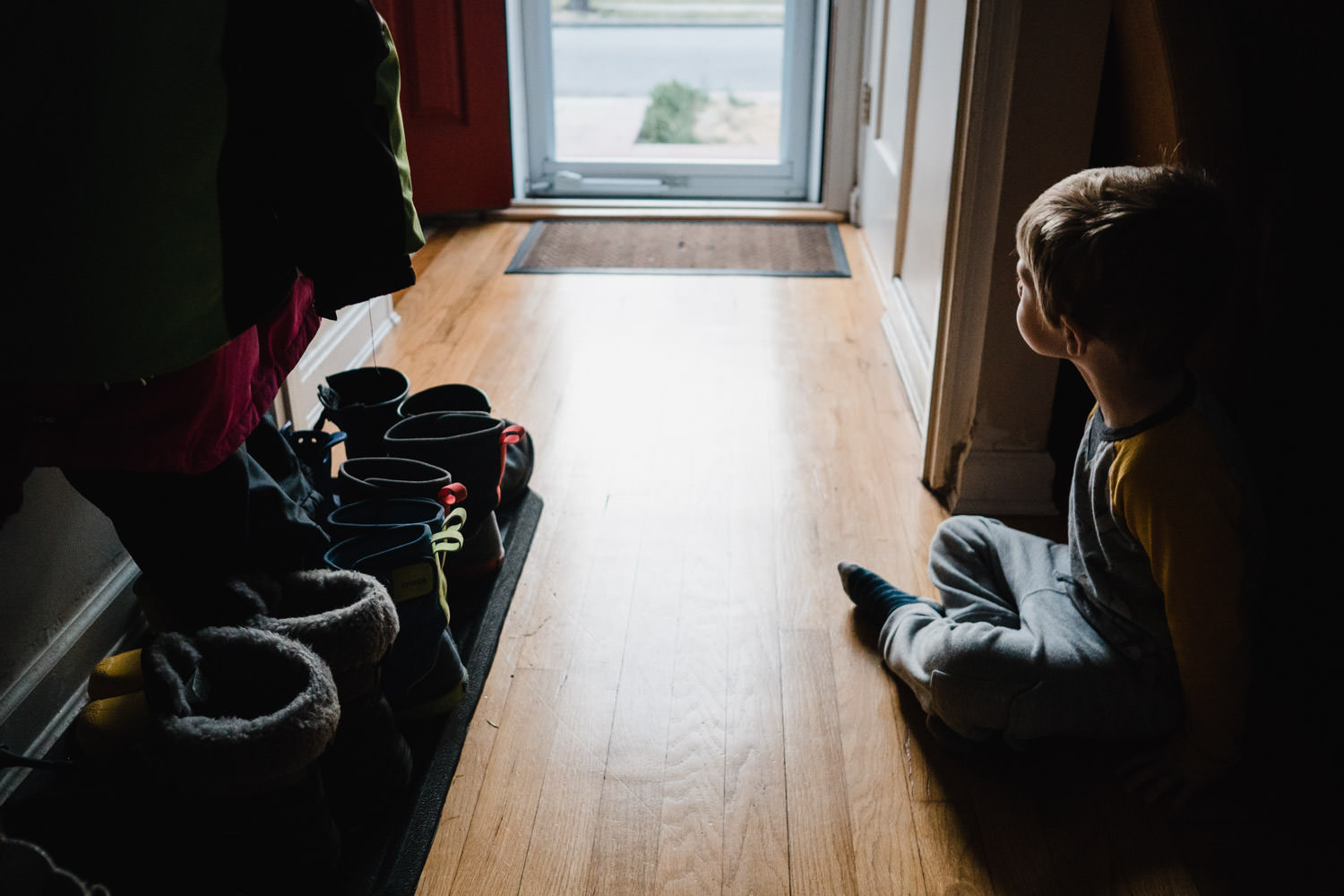 A little boy sits in a hallway and looks out the front door.