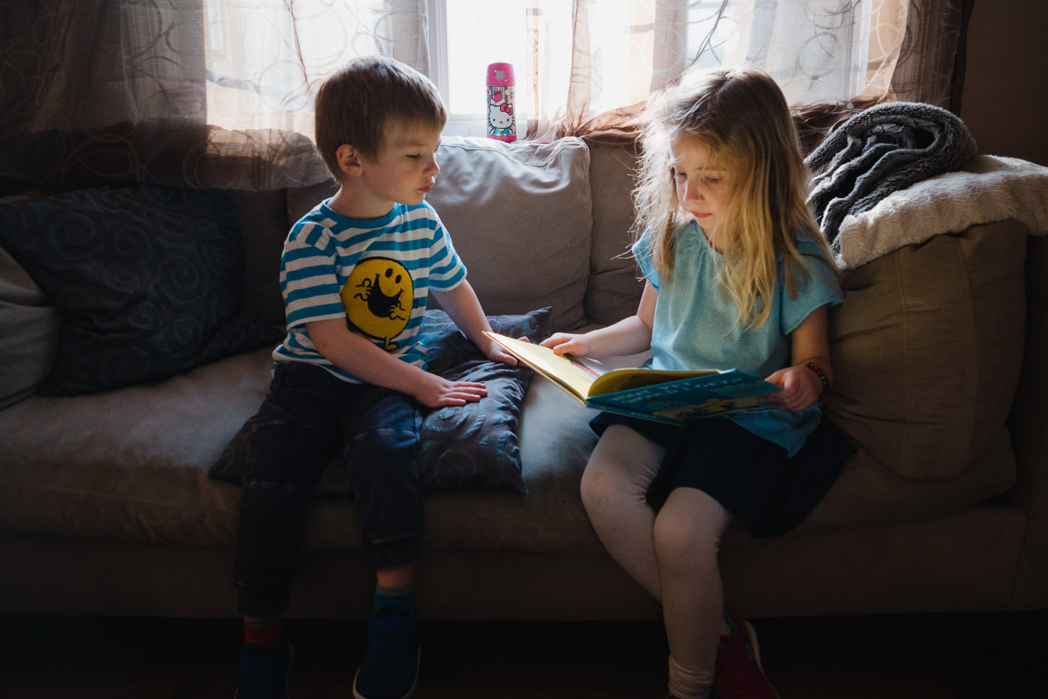 Two children read a book on a couch.