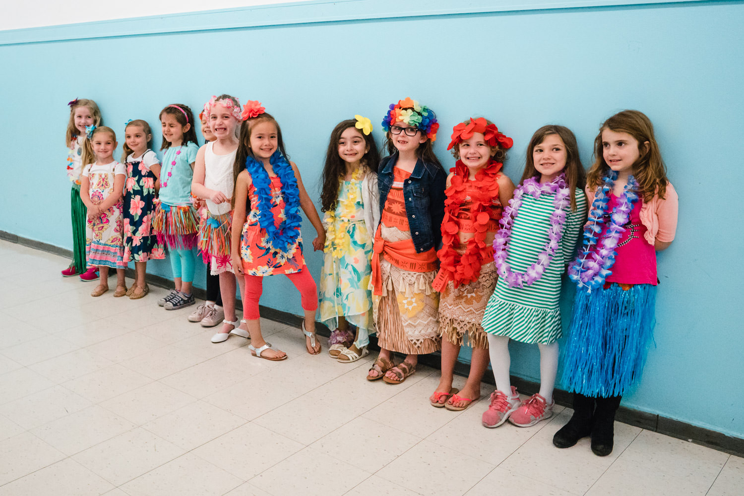 Little girls stand in a hallway dressed for a luau.