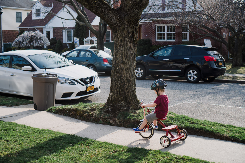 A little boy rides a tricycle down the sidewalk.