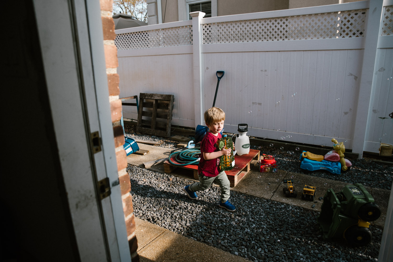 A little boy plays in a side yard.