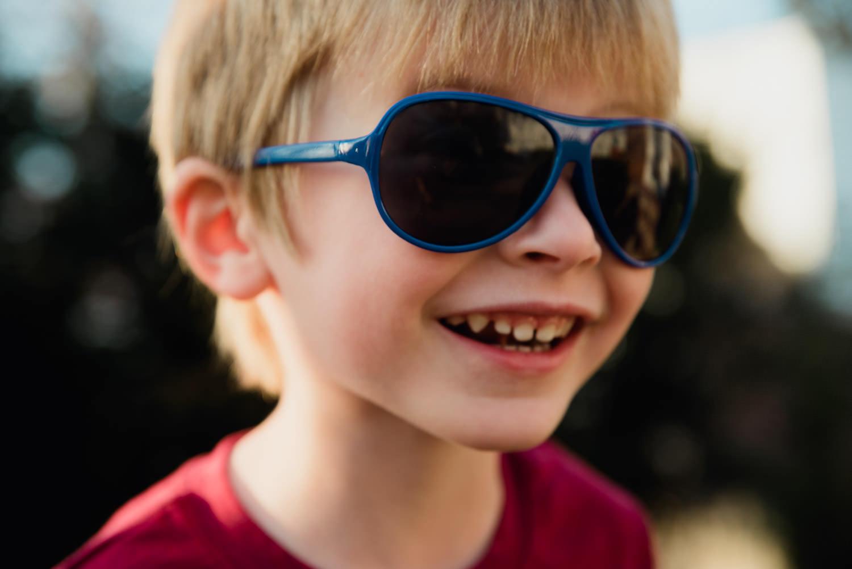 A little boy in sunglasses.