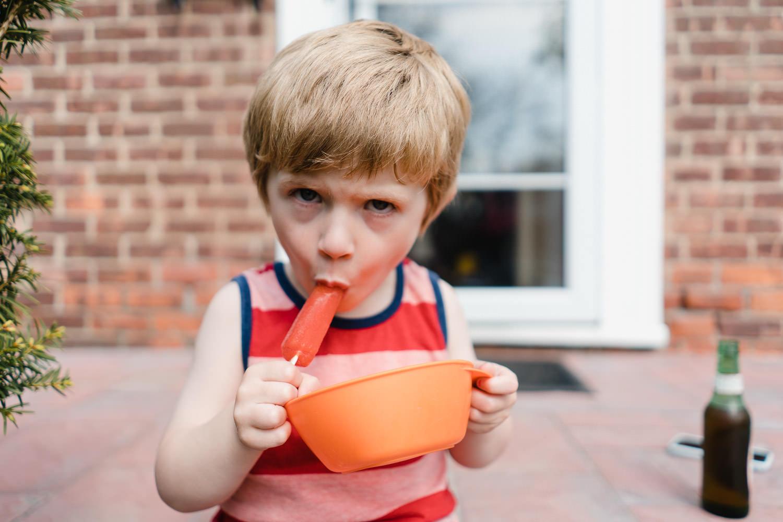 A little boy eats an ice pop on a front porch.