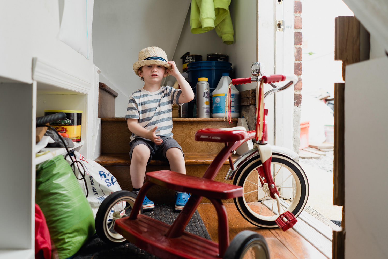 A little boy sits by a side door with his tricycle.