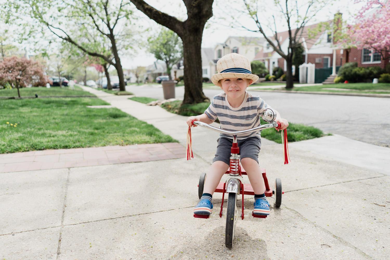 A little boy rides a trike.