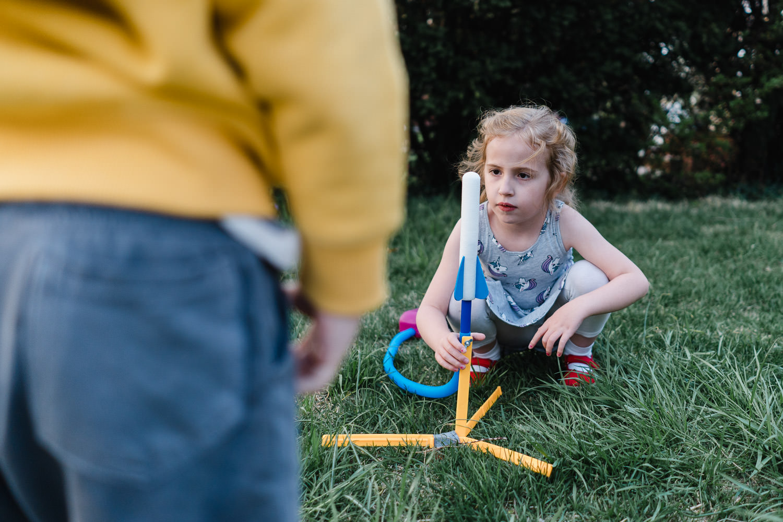 A little girl loads a stomp rocket.