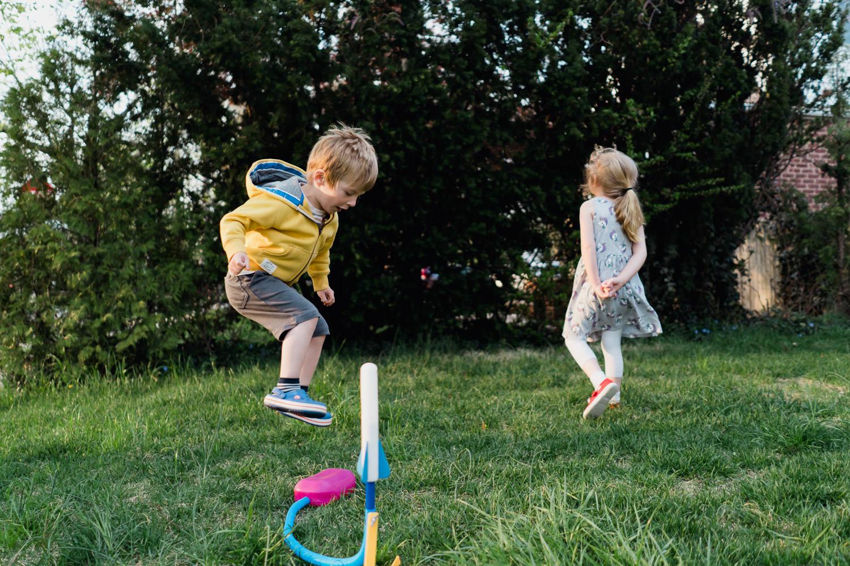 A little boy jumps on a stomp rocket launcher.