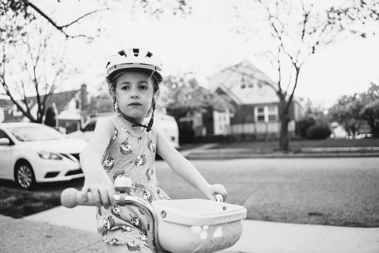 A little girl rides her bike.