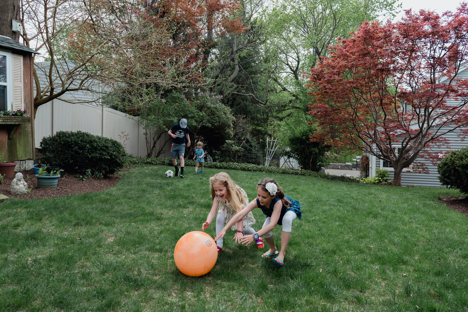 Two little girls chase after an orange ball.