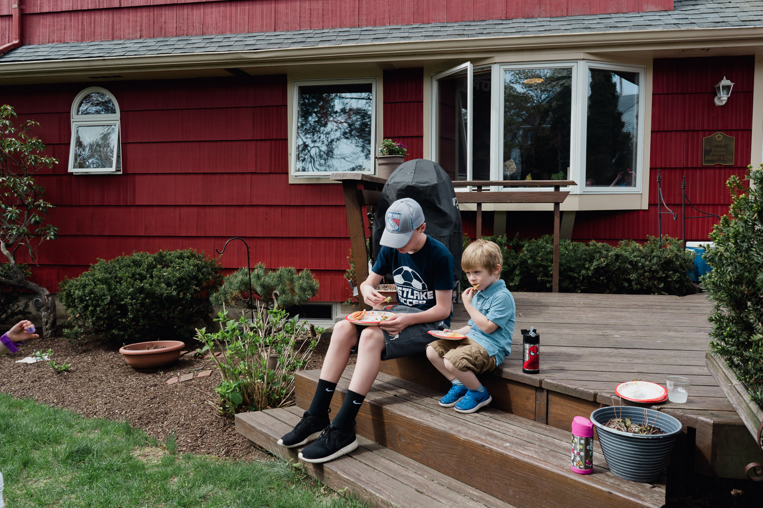 A boy and a toddler sit on some steps and eat a snack.