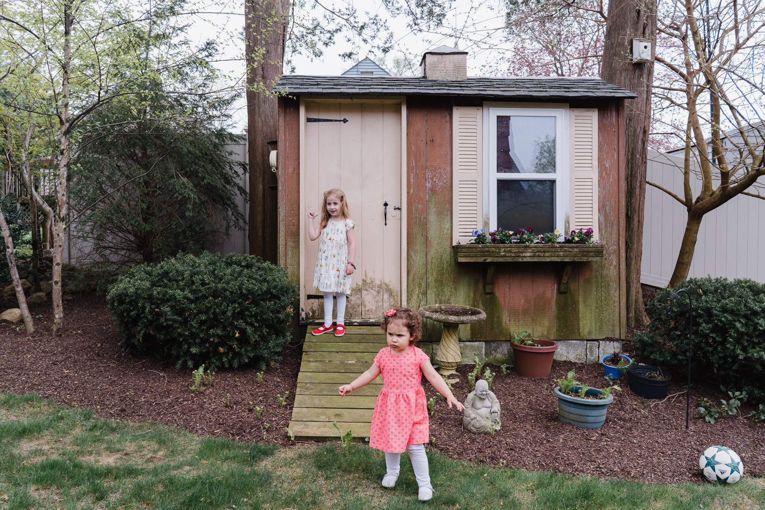 Two girls stand in front of a shed in a backyard.