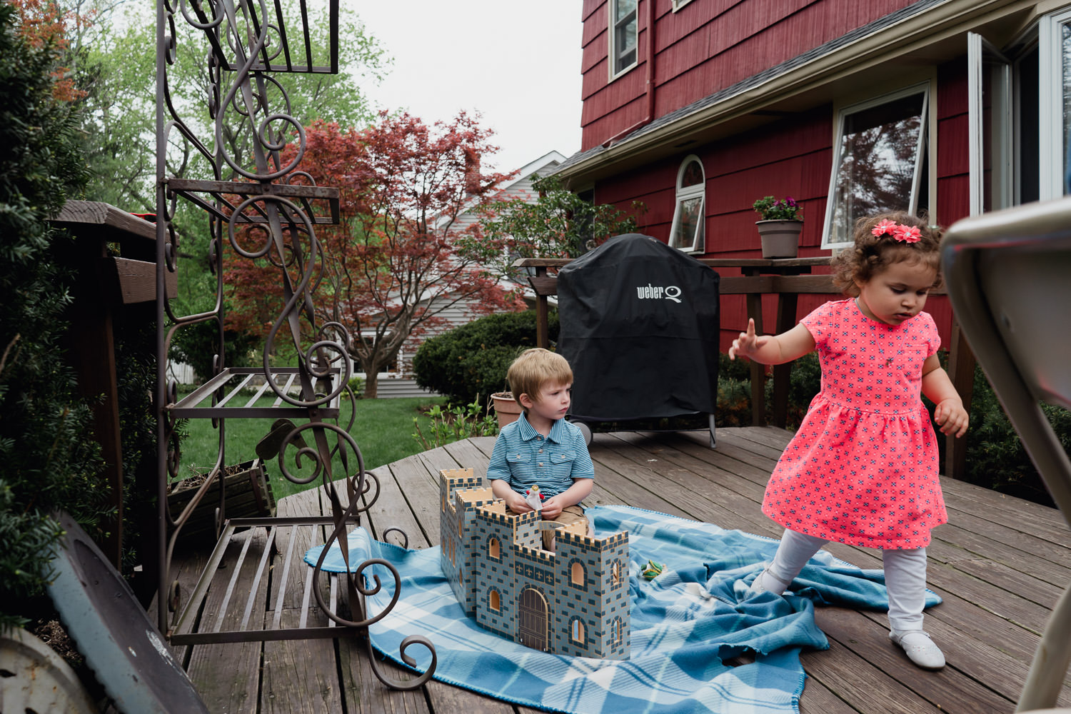 Two little kids play with a toy castle on a back deck.