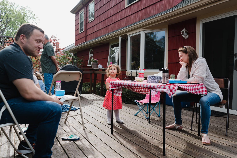 Family members hang outside on a back deck.