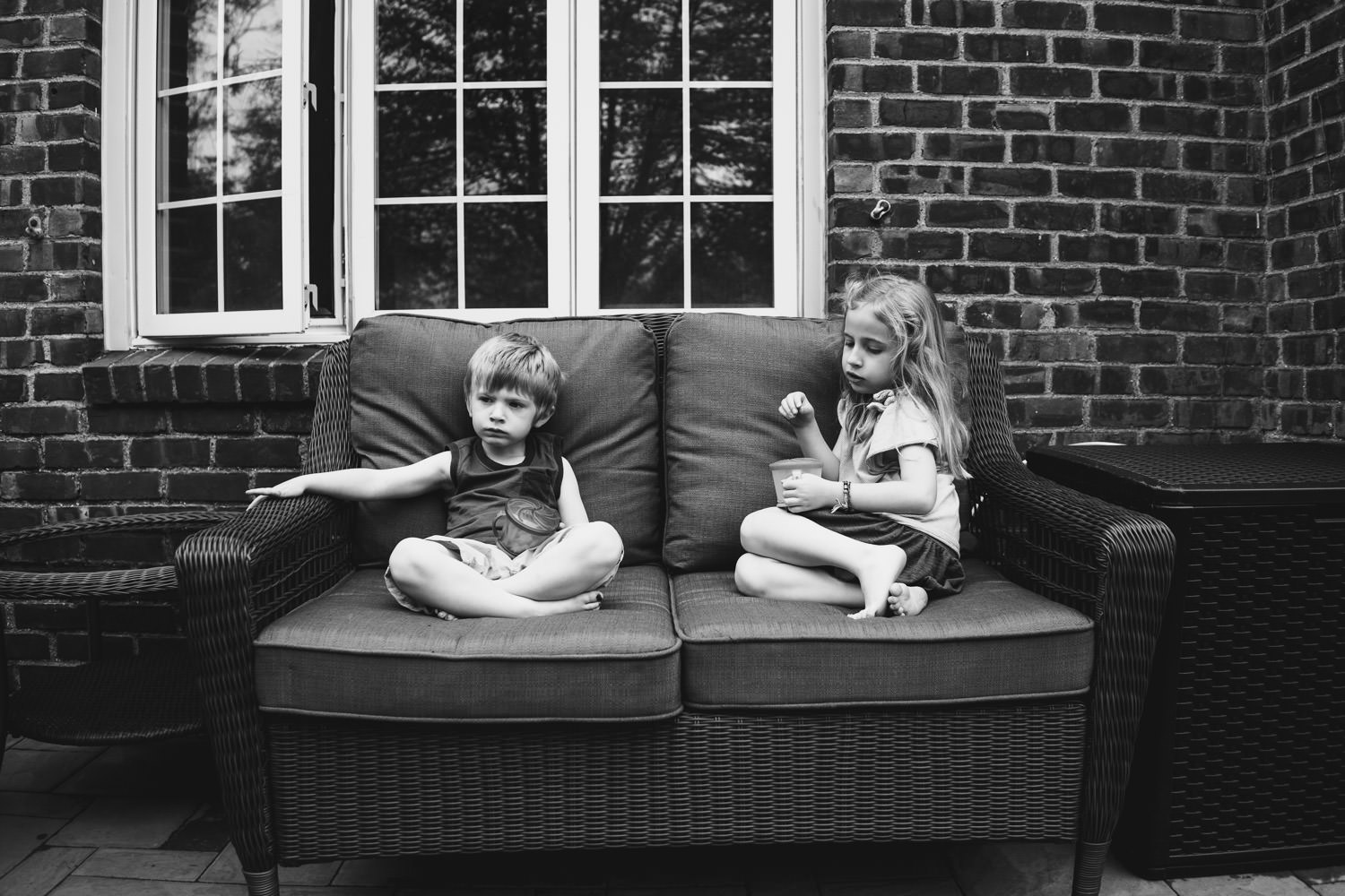 Two kids rest on a loveseat on a front porch.