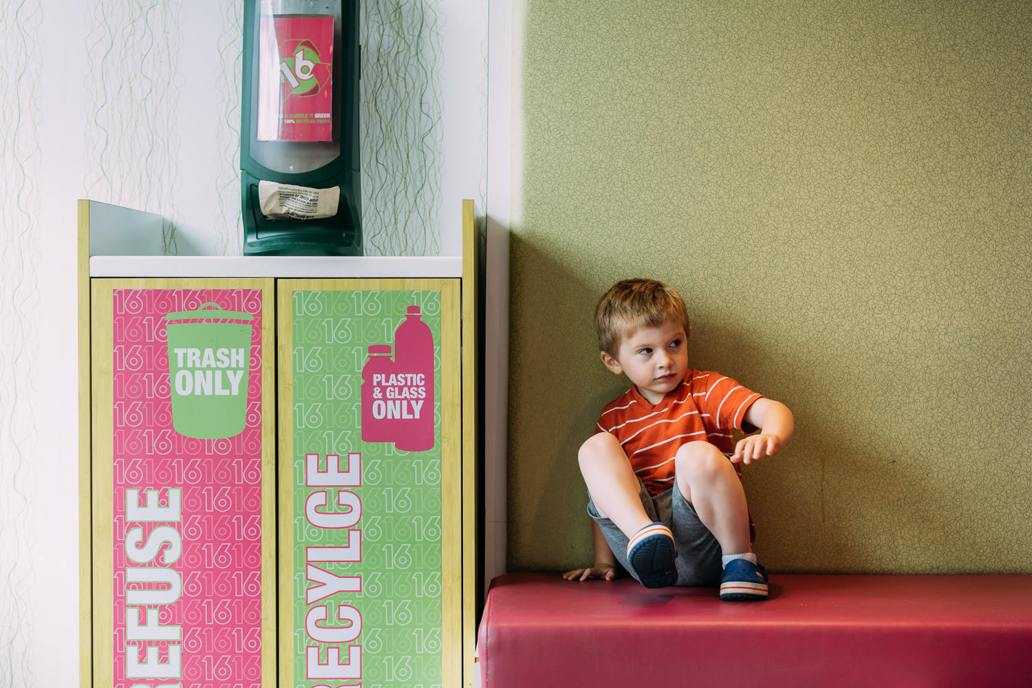 A little boy sits on a bench at 16 Handles.