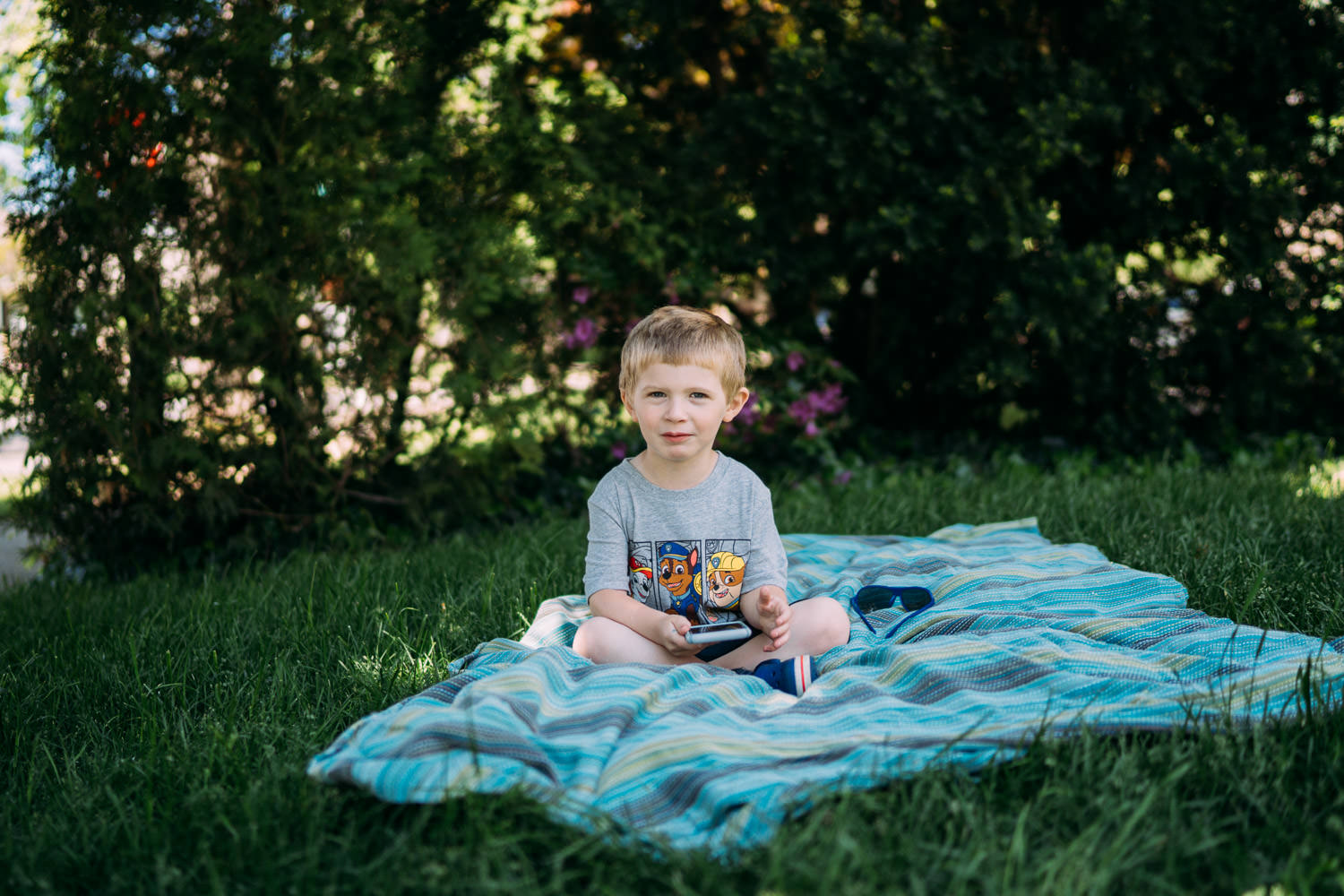 A little boy sits on a blanket on the grass.