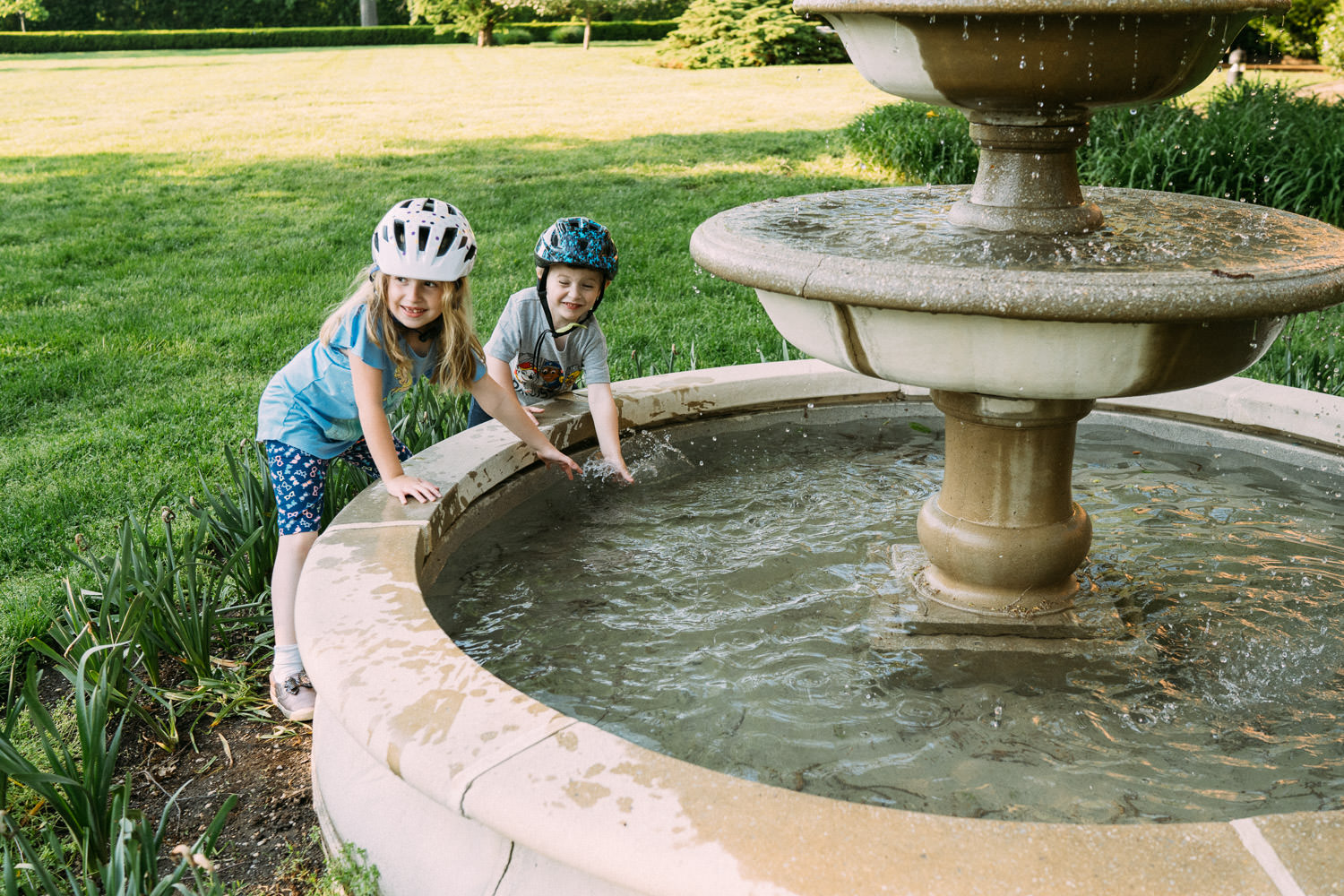 Two children wash their hands in a fountain at Adelphi.